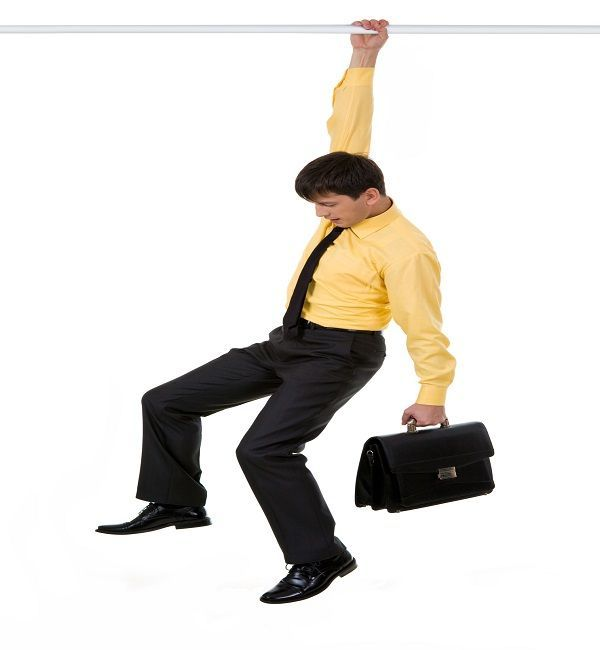 Creative image of frustrated businessman holding by horizontal bar with briefcase in another hand